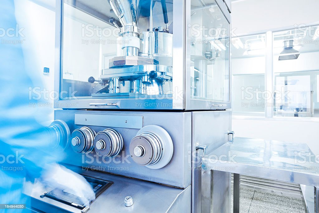 clean room in pharmaceutical factory with technician in blue
