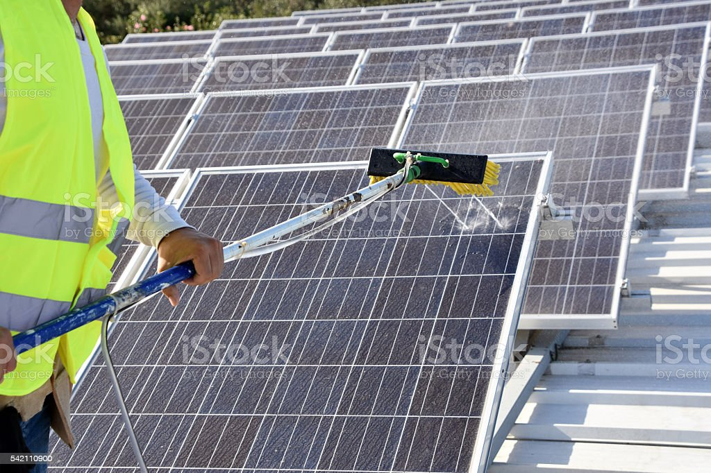Clean solar panels - output rises stock photo
