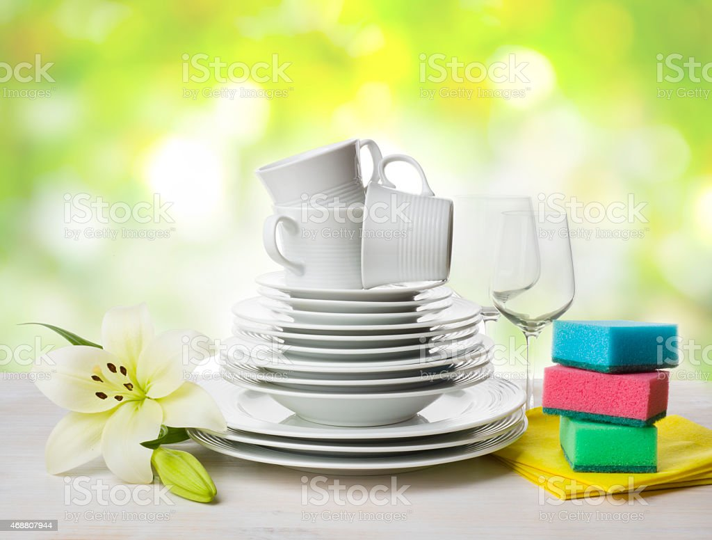 Clean tableware, dishwashing sponges and lily flower over abstract background stock photo
