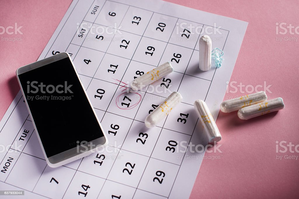 Clean white tampons, calendar and mobile phone on pink background stock photo