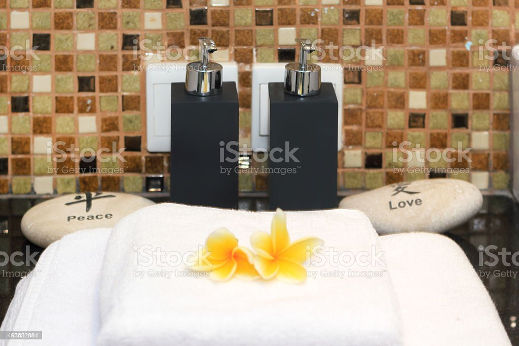 Clean white towel with soap dispenser at spa room stock photo