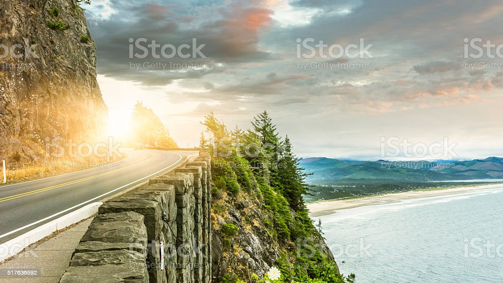 Clean winding road through mountain and ocean stock photo