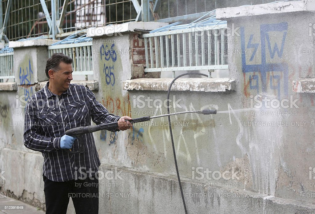 Cleaner cleaning graffiti stock photo