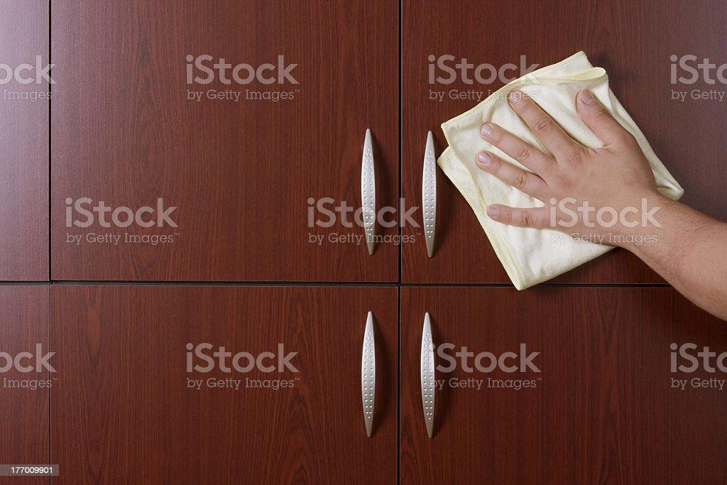 cleaner hand polishing the door of closet stock photo