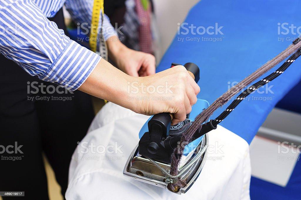 Cleaner in laundry shop ironing jacket stock photo