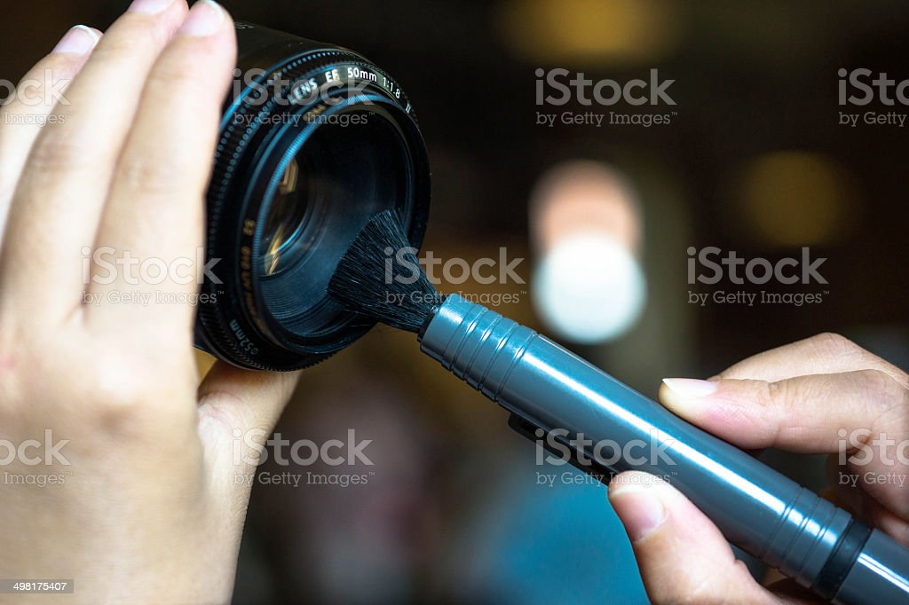 cleaning a lens with a brush stock photo