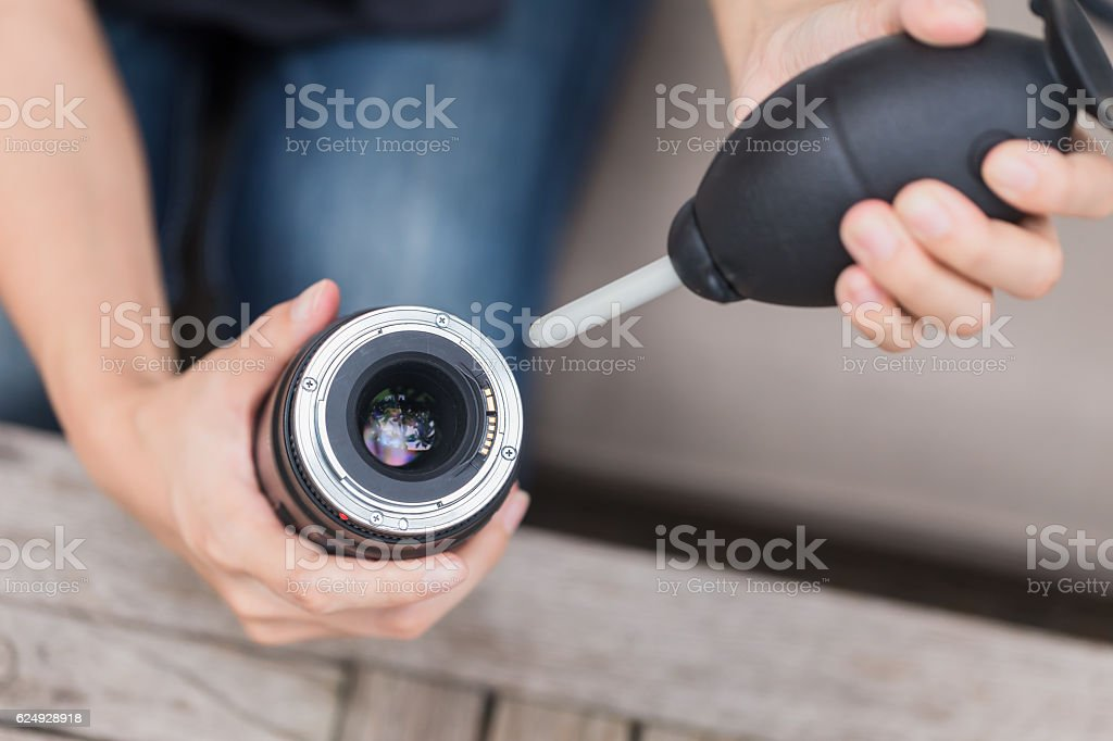 cleaning camera lens with air blower. stock photo