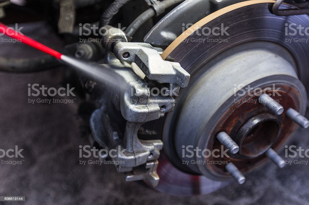 Cleaning car brake pad and disc with caliper stock photo