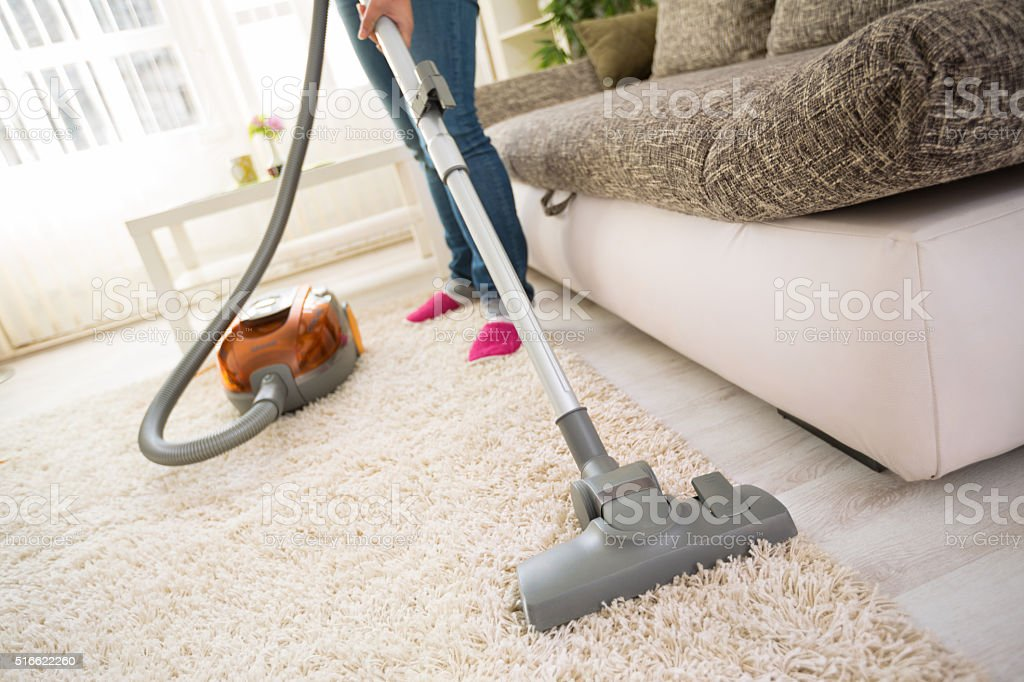Cleaning carpet in living room stock photo