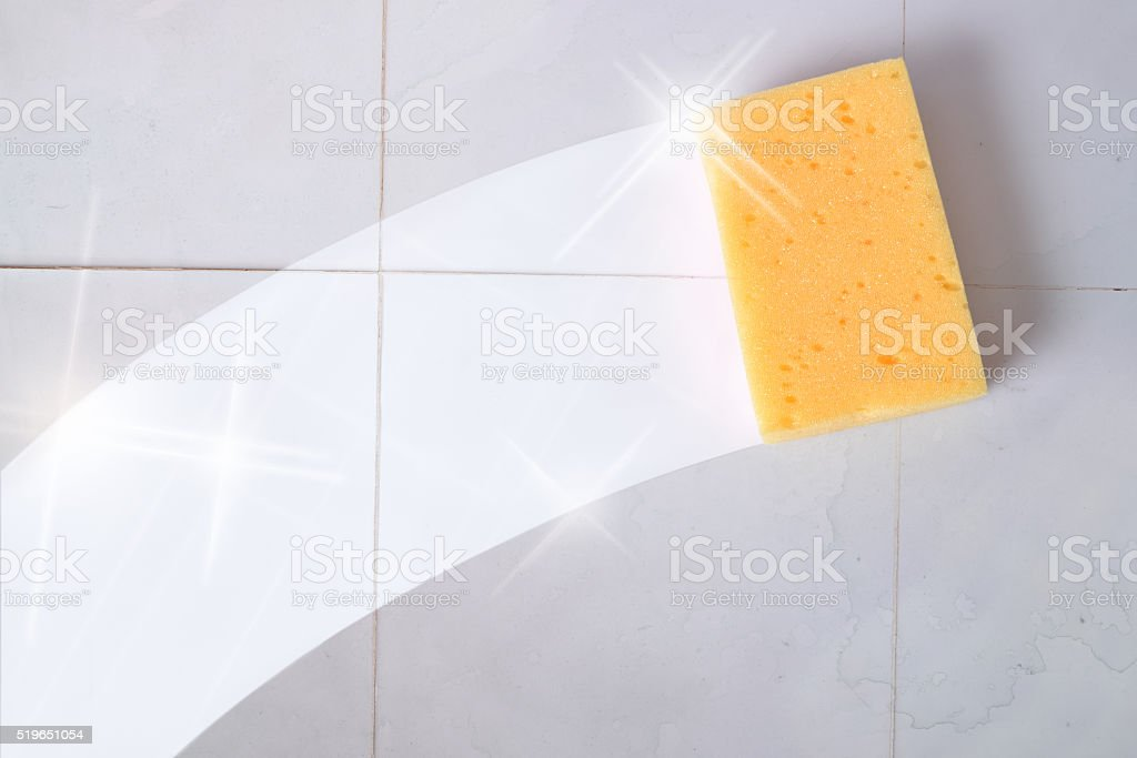 Cleaning concept trace yellow sponge on a dirty gray wall tiles....
