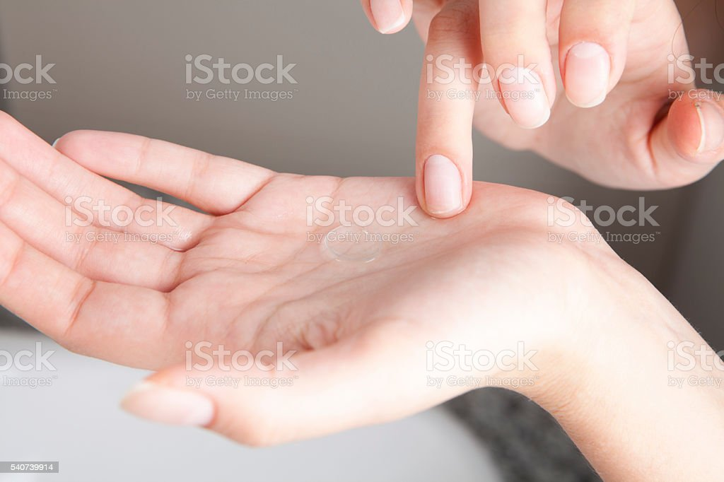 Cleaning contact lenses before putting them on stock photo