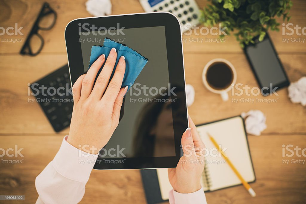 Cleaning digital tablet screen with a cloth stock photo