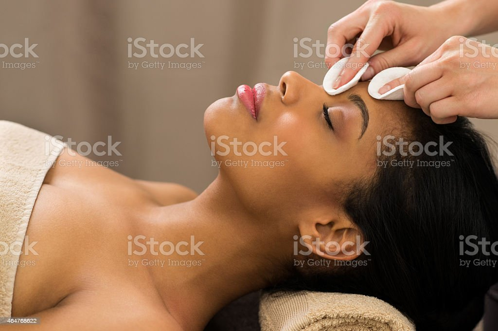 Cleaning face with cotton pads stock photo