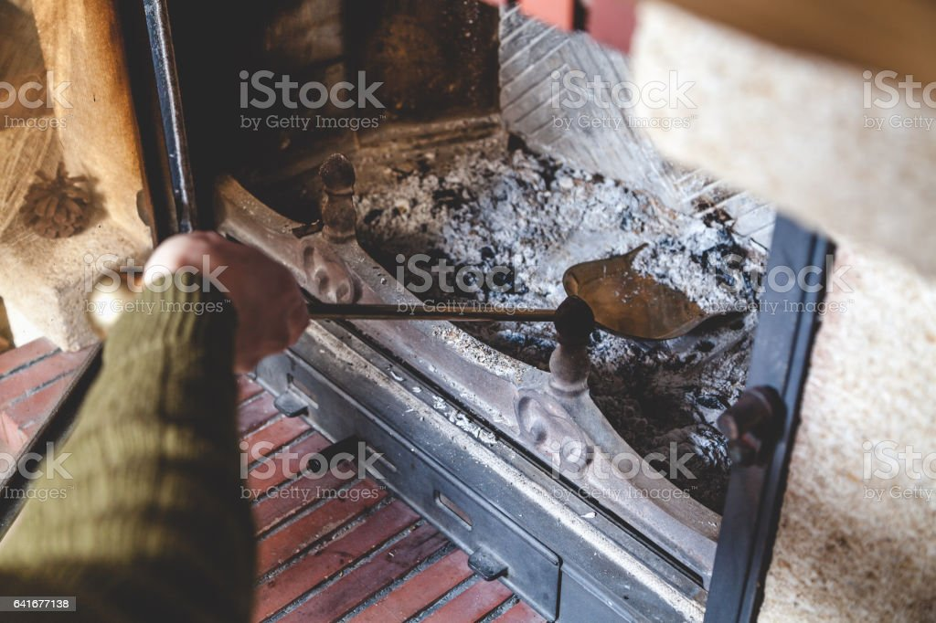 Cleaning  fireplace. hand holding  shovel with ash stock photo