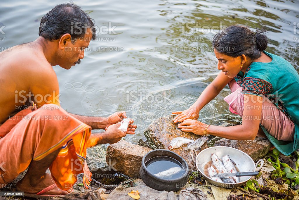 Cleaning fish - traditional lifestyle of Kerala, India stock photo