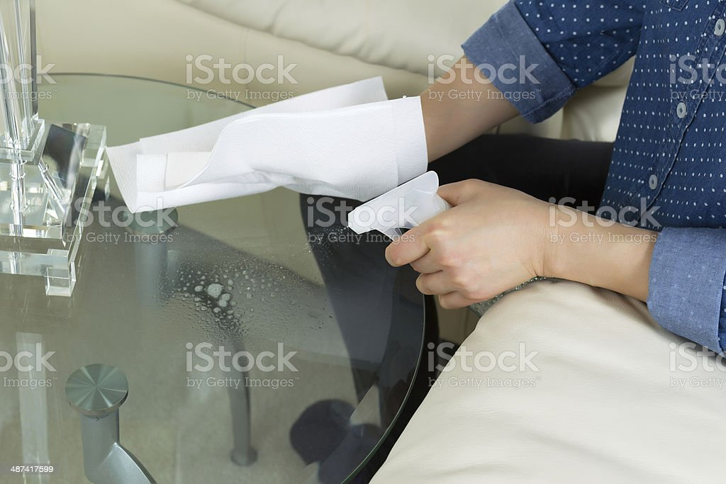 Cleaning Glass End Table next to Sofa stock photo