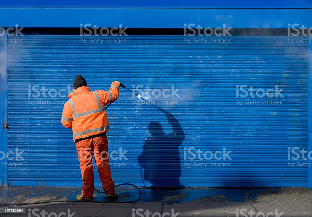 Cleaning graffiti off a security grill. stock photo