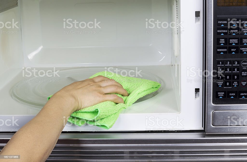 Cleaning inside of Microwave Oven stock photo
