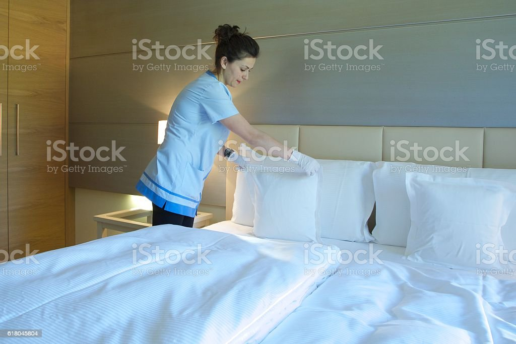 Cleaning lady is making up the bed stock photo