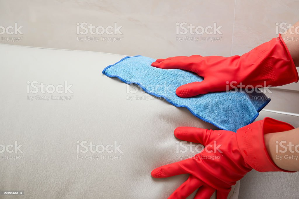 cleaning leather sofa at home stock photo