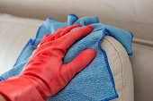 cleaning leather sofa with blue cloth at home