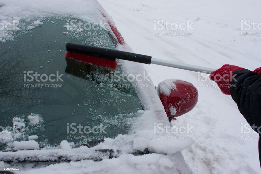 Cleaning off a snowy car window stock photo