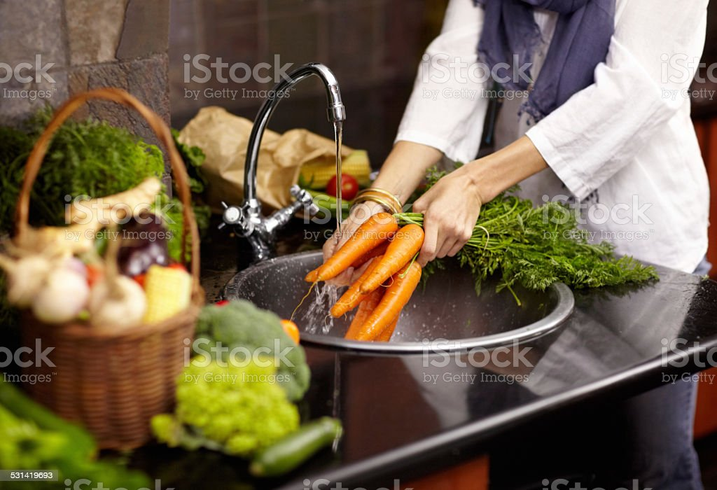 Cleaning off her fresh vegetables stock photo