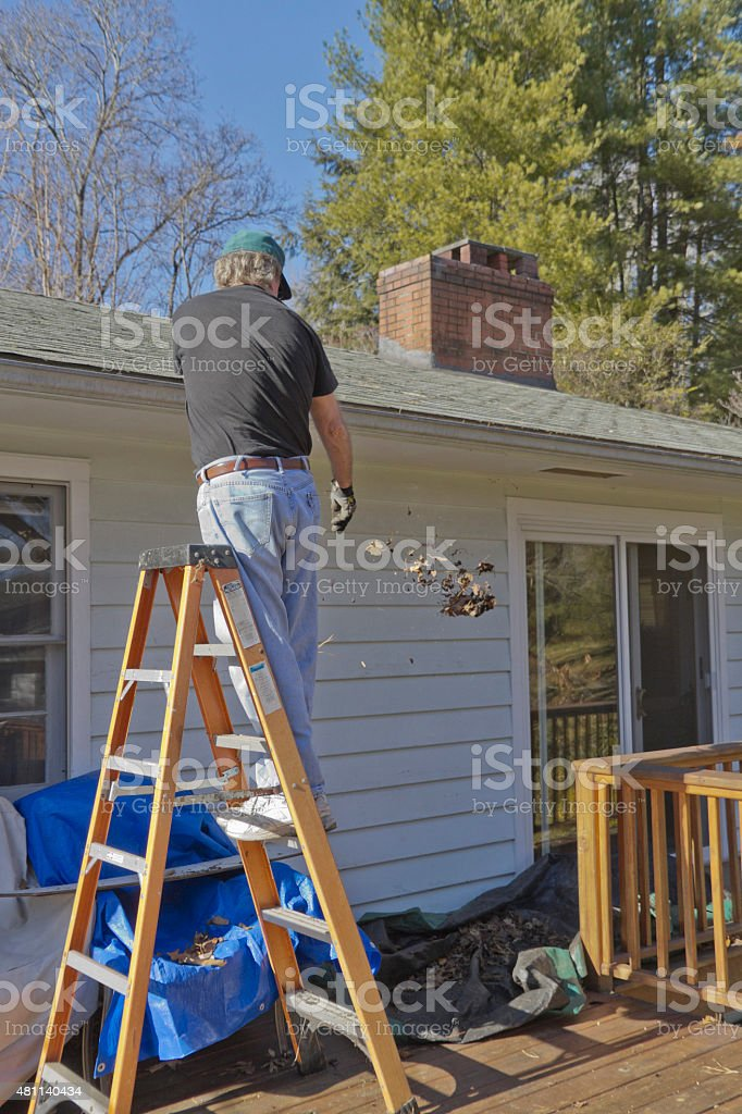 Cleaning Out the Rain Gutter stock photo