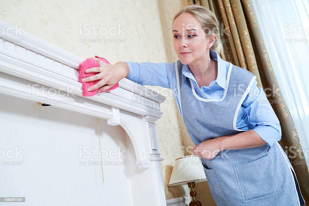 Cleaning service. hotel staff removing dust stock photo