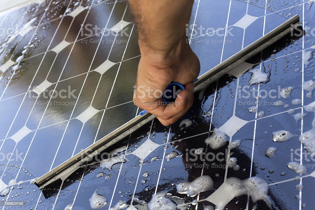 Cleaning solar panel with window cleaner royalty-free stock photo