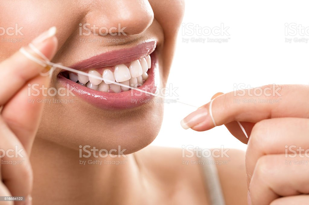 Cleaning teeth with dental floss stock photo