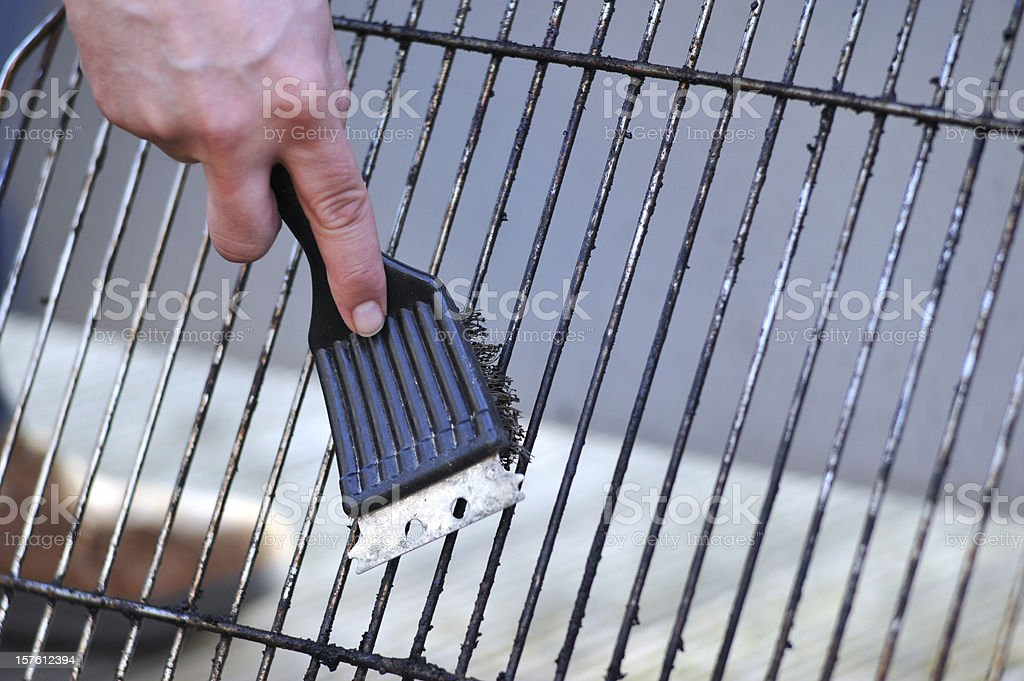 cleaning the grill with scrubber - Grillbürste stock photo