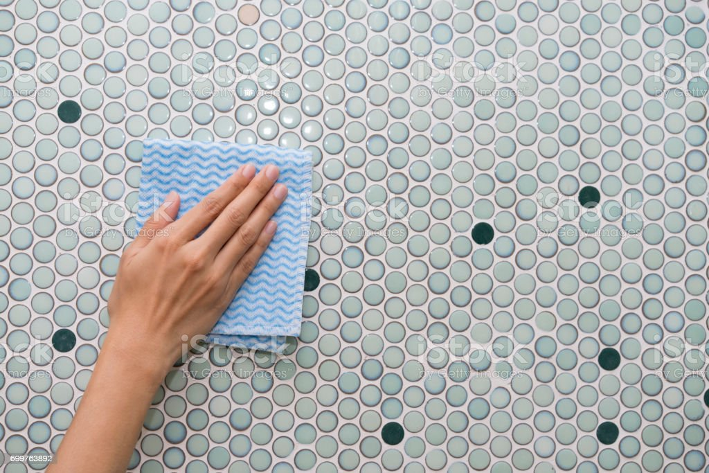 Cleaning tile wall by woman hand
