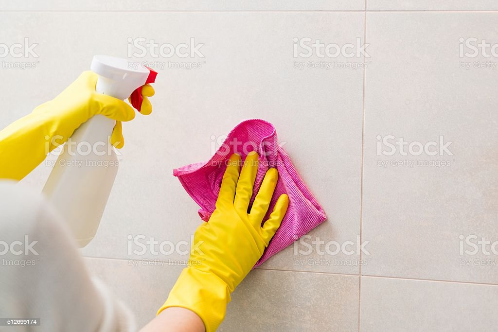 cleaning tiles in bathroom with pink cloth stock photo