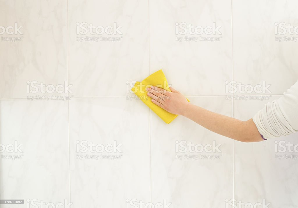 cleaning tiles with a yellow cloth royalty-free stock photo