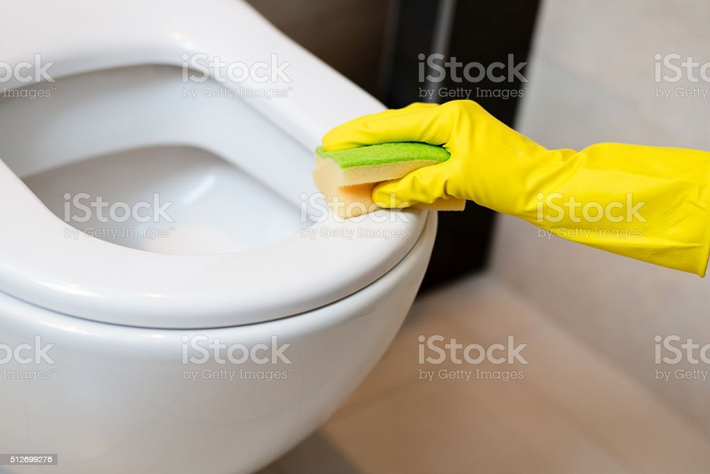cleaning toilet in wc with yellow sponge stock photo