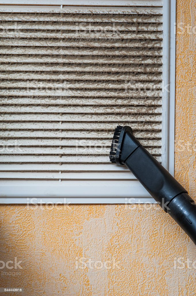 Cleaning ventilation grill with vacuum cleaner stock photo