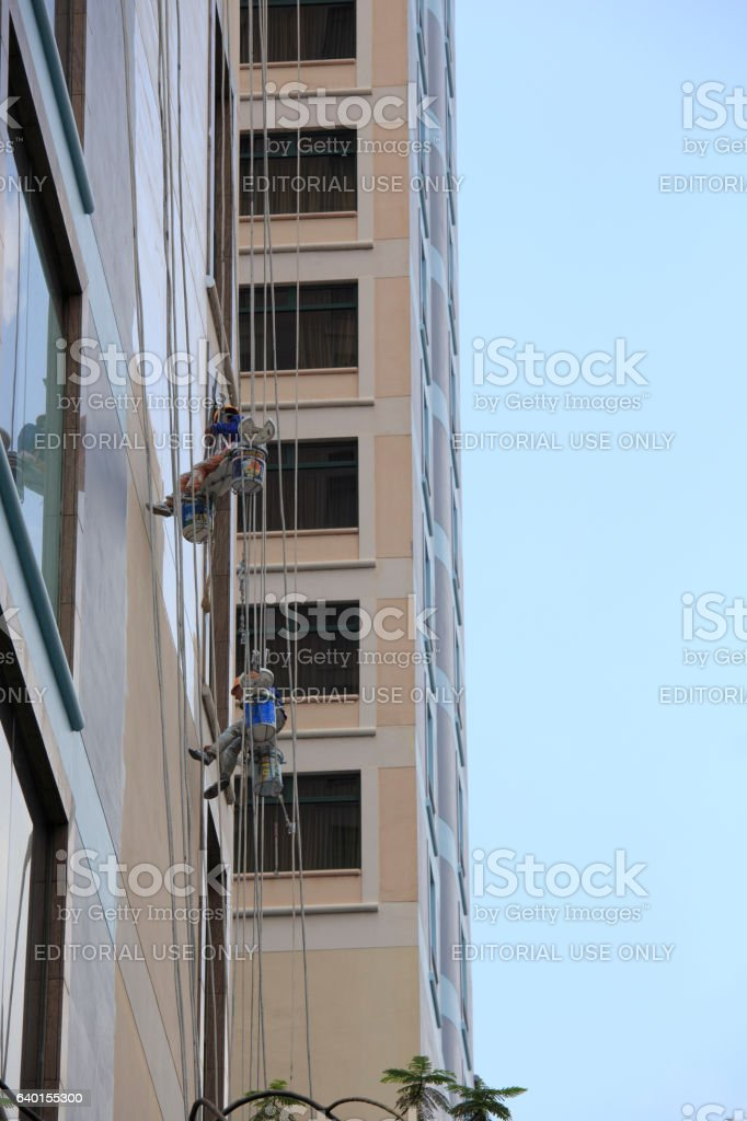 Cleaning windows on the side of a high rise building stock photo