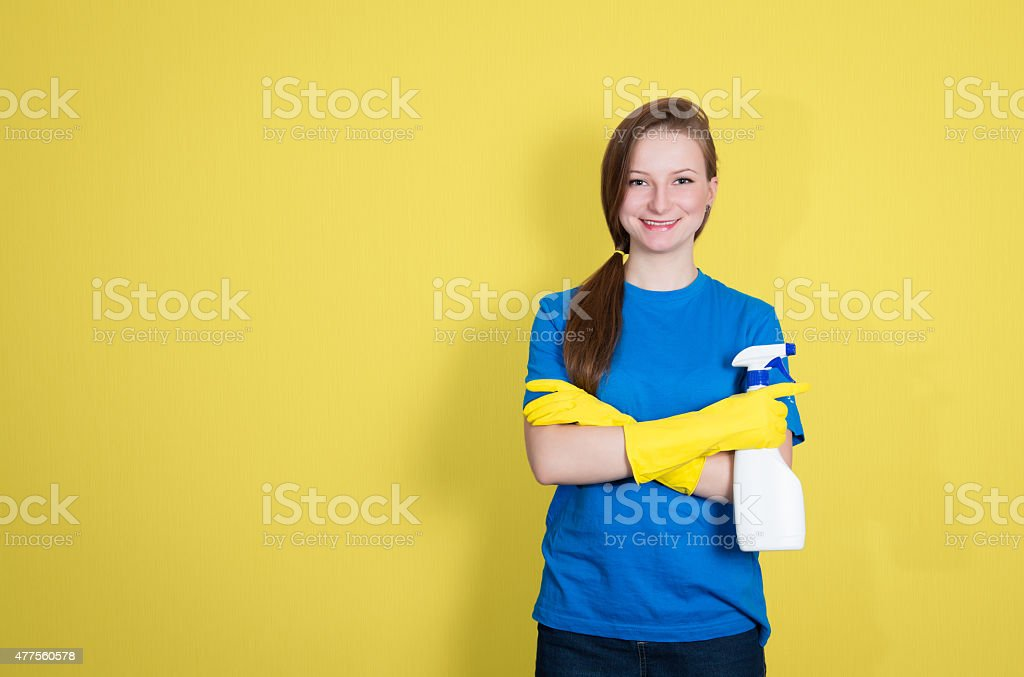 Cleaning woman with spray bottle happy smiling on yellow background. stock photo