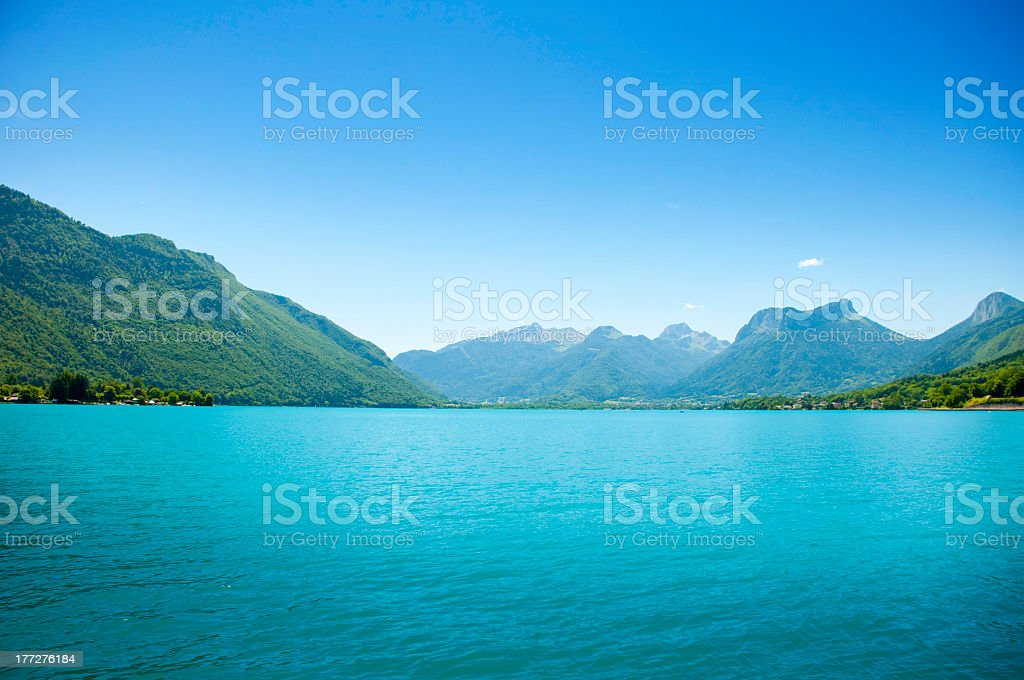 Clear blue Lake Annecy with mountains stock photo