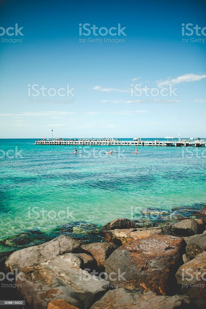 Clear Blue Ocean with Old Pier and People on Paddleboards stock photo