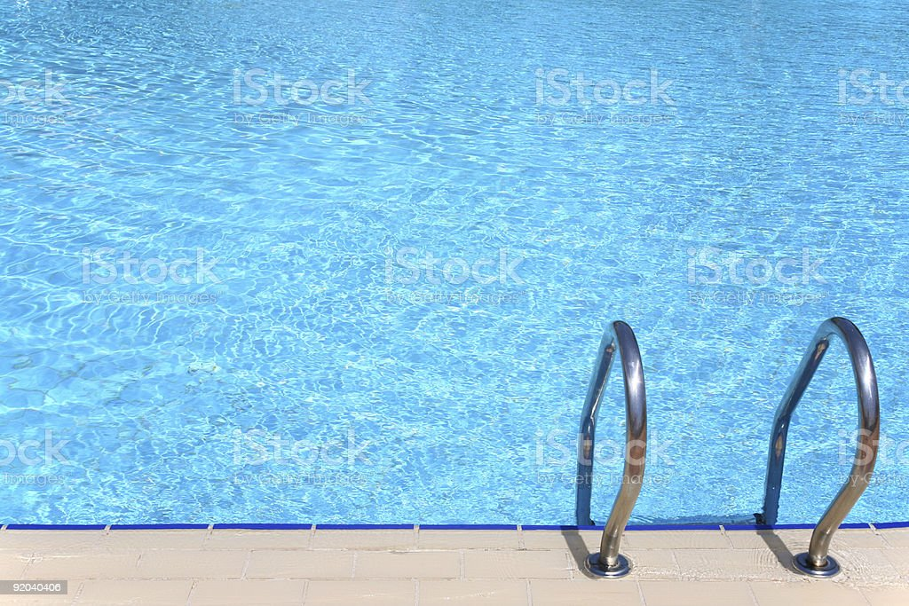 Clear blue pool with metal stair rails stock photo