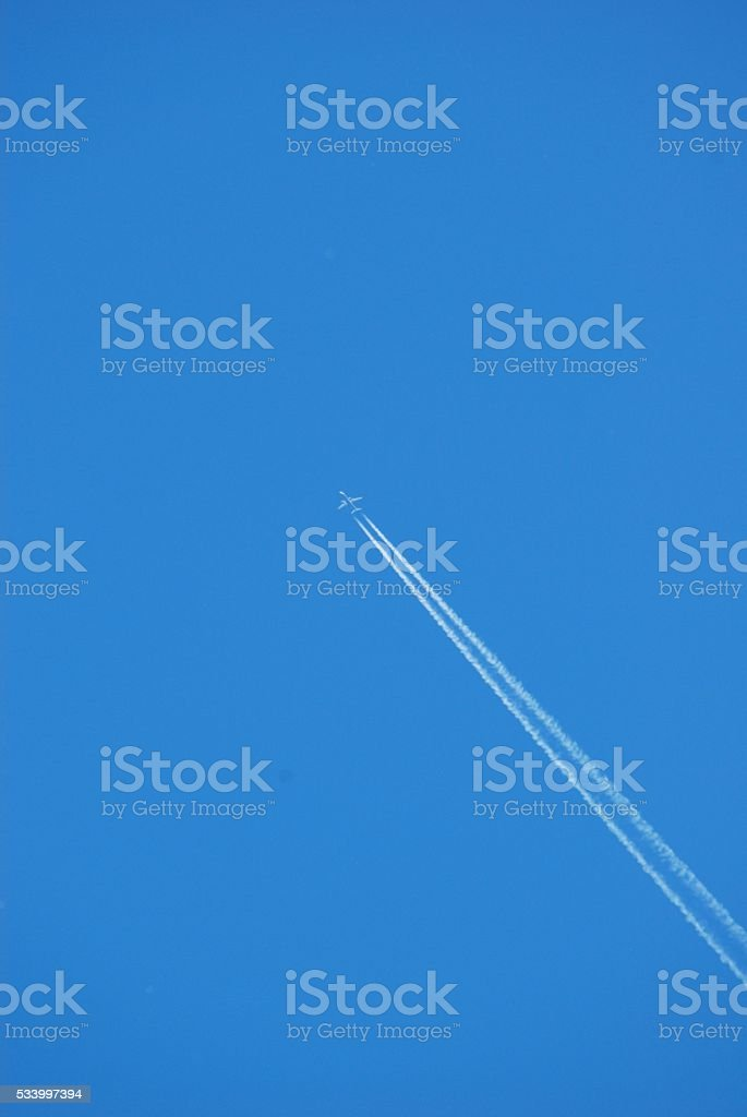 Clear blue sky with aircraft contrail stock photo