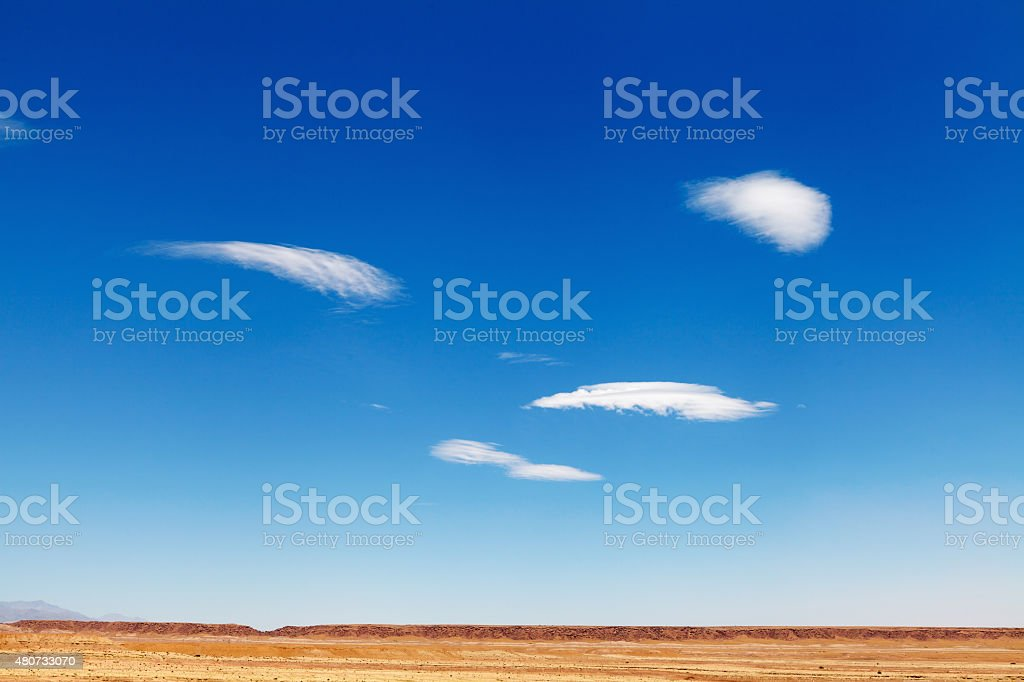 Clear blue sky with few white delicate clouds, above desert stock photo