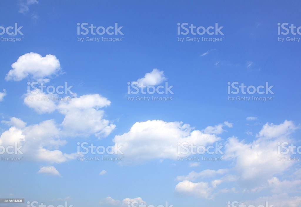 Clear blue sky with scattered clouds stock photo