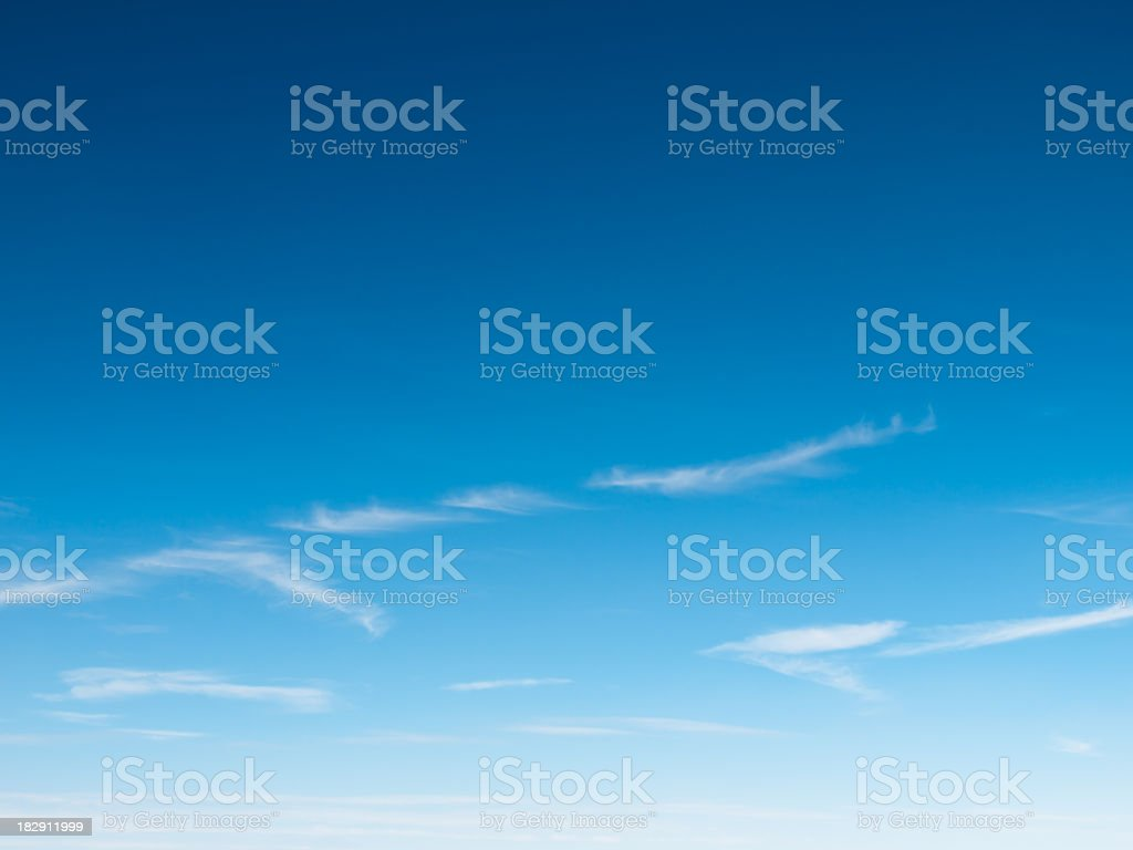 Clear blue sky with wisps of clouds royalty-free stock photo
