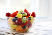 Clear bowl of sliced summer fruits on a dish towel