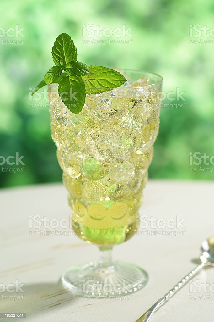 A clear bubble glass full of iced green tea with mint stock photo
