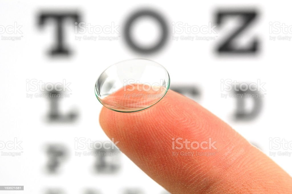 Clear contact lens on fingertip with eye chart stock photo