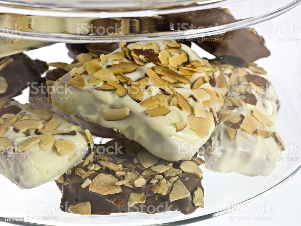 A clear container of light and dark toffee with nuts on top. stock photo